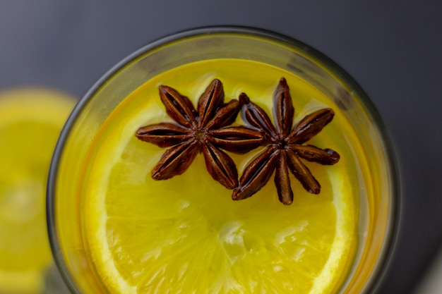 Natural orange vitamin tea with star anise and cinnamon in a transparent glass cup