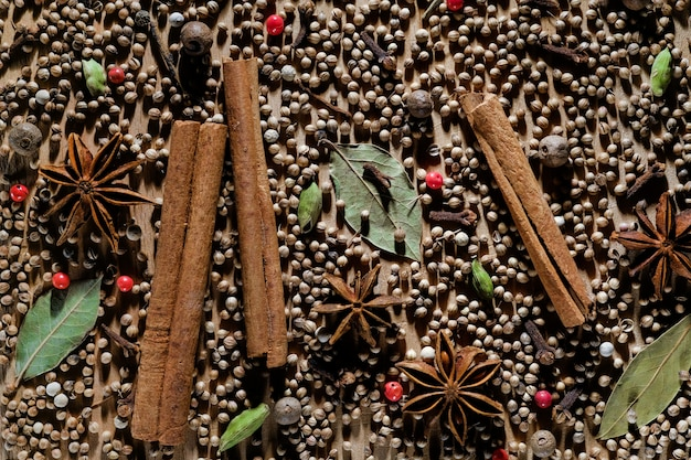 Natural organic aromatic spices are scattered on a wooden board.
