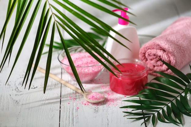 Natural organic bath products. towel, soap, shampoo bottle and leaves.