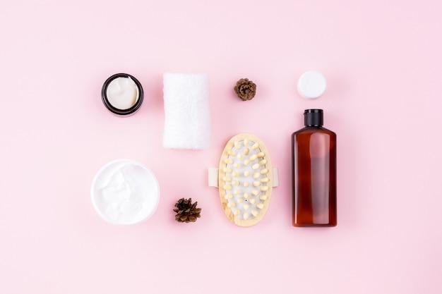 천연 유기농 아름다움 개념. 샴푸 또는 화장품 로션 병, 수건, 오픈 크림 용기, 마사지기. 분홍색 표면에 스킨 케어 제품. 창의적인 바디 케어 레이아웃. 뷰티, 스파 플랫 누워.
