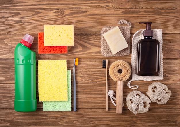 Натуральные органические чистящие средства по сравнению с обычным токсичным моющим средством, синтетическими губками и пластиковой щеткой. концепция этических нетоксичных экологически чистых товаров для дома. вид сверху, деревянный фон