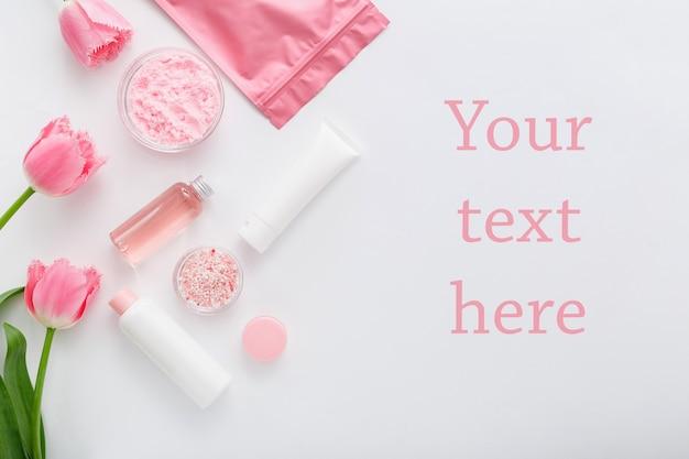 白い背景にピンクの花を持つ天然有機化粧品。美容、バススパ用自然化粧品、スキンケア、コピースペース付きフラットレイ、モックアップ。クリームローションパウダーウェルネス製品。