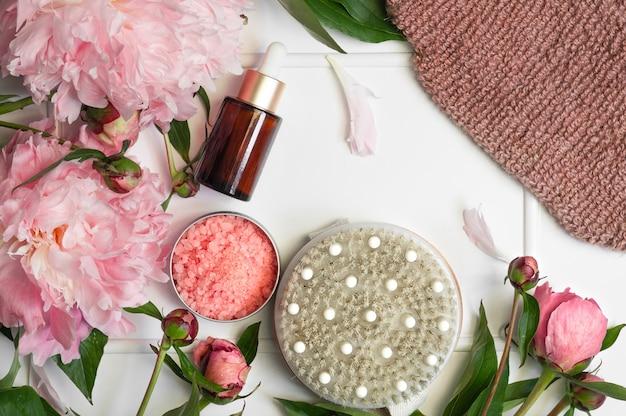 白い背景にピンクの牡丹の花を持つ天然有機化粧品。スパリラックストリートメントとアンチセルライトマッサージ。美容、バススパ用自然化粧品、スキンケア、フラットレイ。