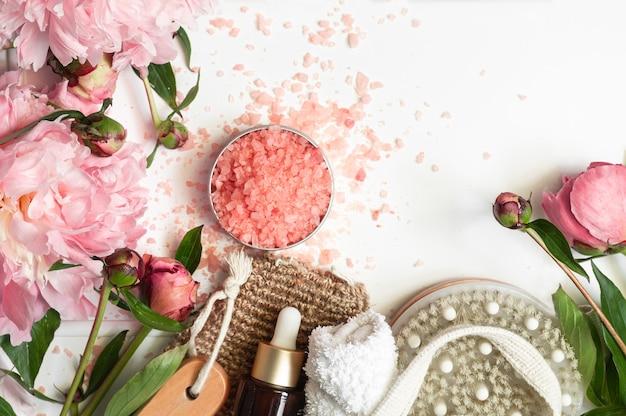 흰색 바탕에 분홍색 모란 꽃과 천연 유기농 화장품. 스파 릴랙스 트리트먼트 및 안티 셀룰 라이트 마사지. 미용, 목욕 스파, 스킨 케어, 플랫 레이 용 천연 화장품.