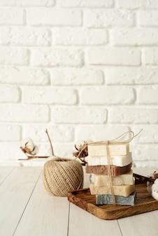 Натуральная органическая косметика. стек мыла ручной работы на белом деревянном фоне