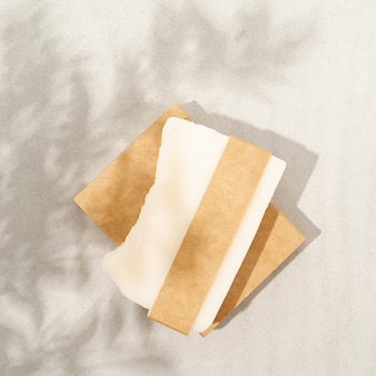 Natural organic cosmetics. top view of handmade soap with craft blank band on white textured background with a shadow