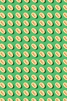 녹색 벽에 수박의 잘라 반쪽에서 천연 유기농 과일 패턴입니다. 기하학적 선 위의 상위 뷰.
