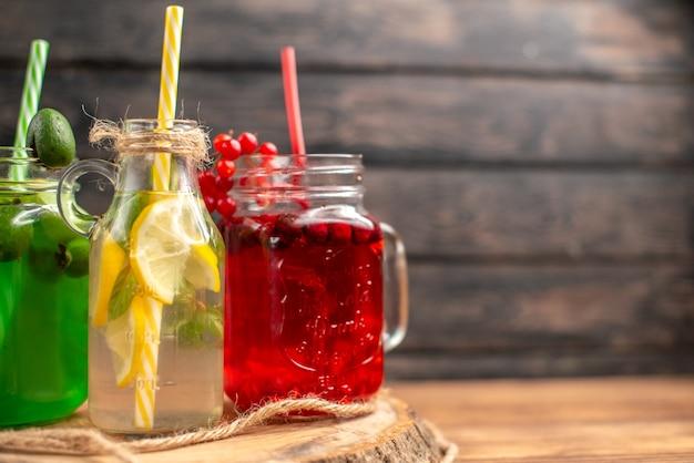 Succhi di frutta biologica naturale in bottiglia serviti con tubi su un tagliere di legno