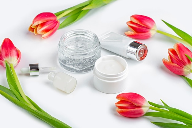 天然オーガニックの自家製化粧品コンセプト。スキンケア、治療、美容製品:白い背景の春の赤いチューリップの花の中でクリームと血清の容器。クローズアップ、テキスト用のスペースをコピー