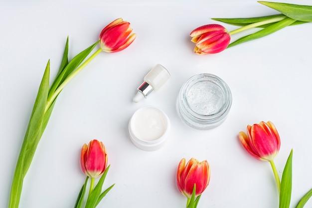 自然な有機自家製化粧品のコンセプトです。スキンケア、治療、美容製品:クリームと美容液を入れた容器で、白い表面に赤いチューリップの花が咲き乱れます。フラット横たわっていた、テキストのコピースペース