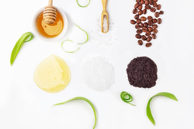 Натуральные органические ингредиенты домашнего ухода за кожей. очищающая и питательная косметика. косметические продукты: крем, мед, кофейный скраб, среди зеленых листьев на белом фоне. закройте, скопируйте пространство для текста