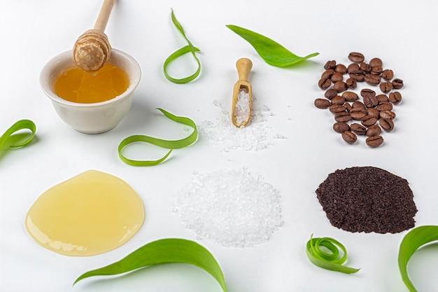 Натуральные органические ингредиенты домашнего ухода за кожей. очищающая и питательная косметика. косметические средства: крем, мед, кофейный скраб, среди зеленых листьев на белом фоне