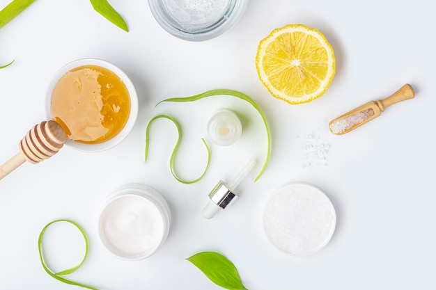 Natural organic ingredients to make home skin care. cleansing and nourishing cosmetics. beauty products: cream, honey, sea salt among green leaves on white surface. flat lay, copy space for text