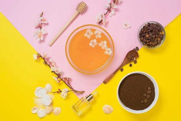 天然有機成分-海塩、コーヒースクラブ、蜂蜜、黄色の背景にハードボディブラシ。セルライトのホームスキンケア。スキンケアのコンセプト、ホームスパ。上からの眺め。