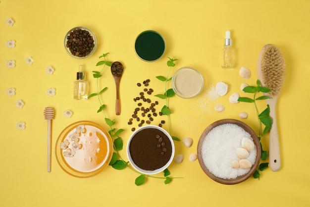 天然有機成分-海の塩、コーヒースクラブ、蜂蜜、黄色の背景にハードボディブラシ。上からの眺め。