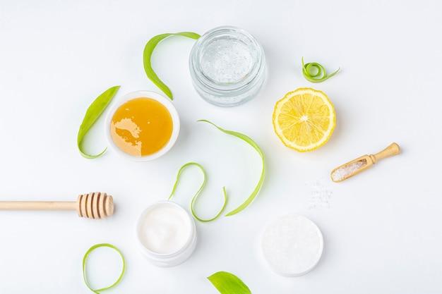 Натуральные органические ингредиенты для домашнего ухода за кожей. очищающая и питательная косметика. косметические продукты: крем, мед, морская соль среди зеленых листьев на белом фоне. закройте, скопируйте пространство для текста