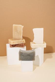 천연 유기농 셀프 케어 제품. 크림 배경에 흰색 연단에 다른 수제 비누 구성. 베이지 색 배경에 스파 액세서리 창조적 인 예술 구성