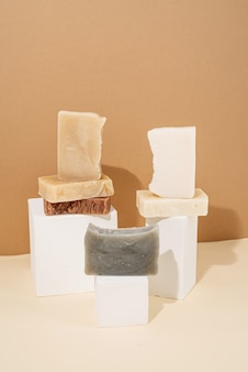 Natural organic selfcare products. different handmade soaps composition on white podiums on cream background. spa accessories creative art composition on beige background