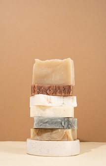 Natural organic selfcare products. tower stack of different handmade soaps on cream background. spa accessories creative art composition on beige background