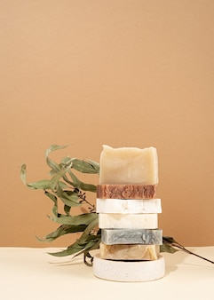 천연 유기농 셀프 케어 제품. 다른 수 제 비누와 크림 배경에 잎의 타워 스택. 베이지 색 배경에 스파 액세서리 창조적 인 예술 구성