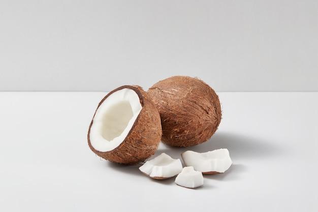 밝은 회색 이중 톤 배경, 복사 공간에 절반 및 작은 조각으로 잘 익은 신선한 코코넛 과일에서 천연 유기농 세트. 채식 개념.