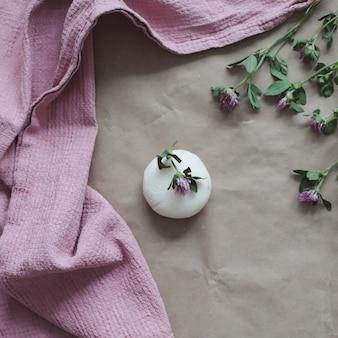 꽃과 분홍색 수건이 있는 천연 유기농 비누