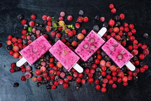 Натуральный органический сорбет четыре мороженого на палочке с черной смородиной и красными ягодами вокруг. холодный молочный фруктовый десерт летом