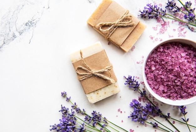 ラベンダー入りの天然オーガニックspa化粧品。大理石の背景にフラットレイバスソルトとラベンダーの花。スキンケア、美容トリートメントのコンセプト