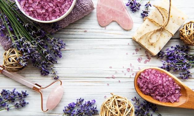 ラベンダー入りの天然オーガニックspa化粧品。木製の背景にフラットレイバスソルト、スパ製品、ラベンダーの花。スキンケア、美容トリートメントのコンセプト