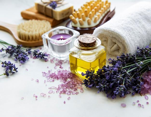 ラベンダー入りの天然オーガニックspa化粧品。木製のテーブルにフラットレイバスソルト、スパ製品、ラベンダーの花。スキンケア、美容トリートメントのコンセプト