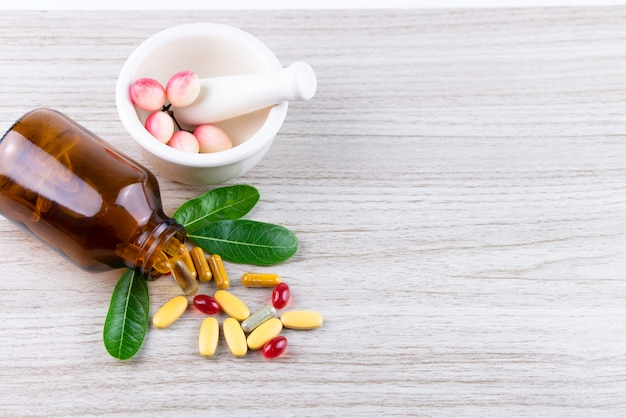 Natural organic vitamin and supplements, leaf in mortar on wooden background, medicine and drug concept