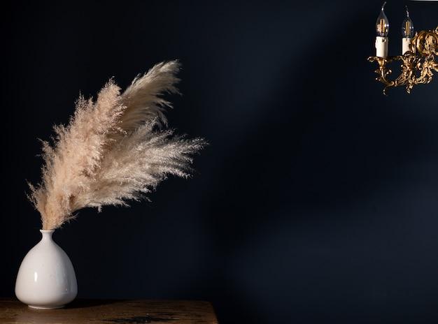 Натуральная трава пампасов в вазе на деревянном винтажном коричневом столе на темно-синем фоне в винтажном стиле