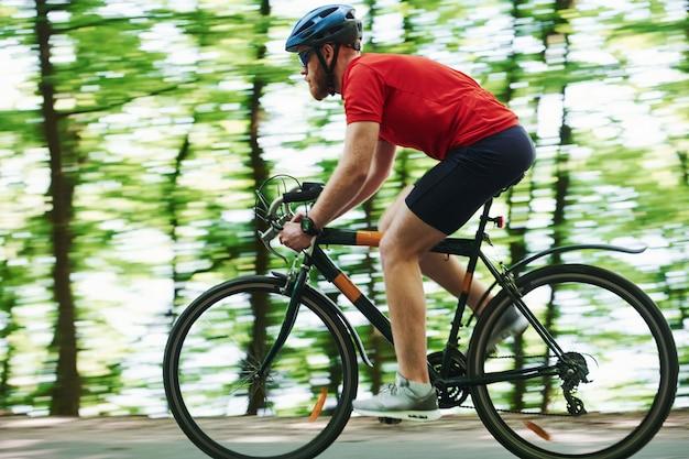 自然公園。自転車のサイクリストは晴れた日に森のアスファルト道路に
