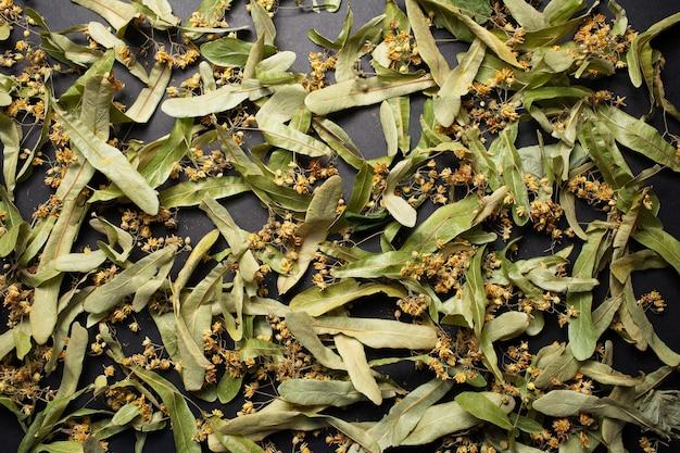 Natural pattern of dry linden flowers for tea, on black background.