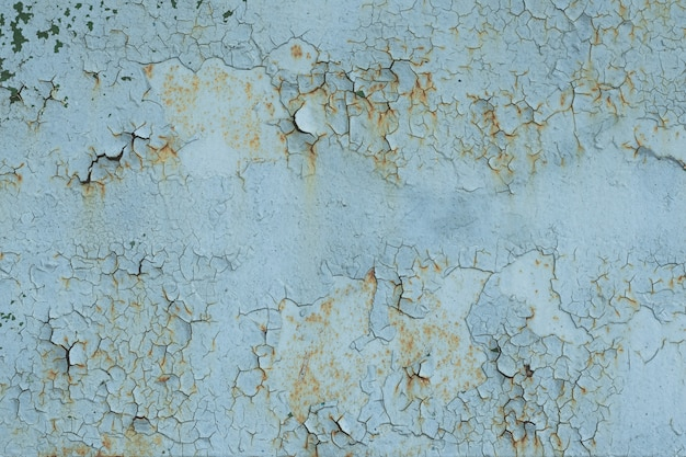 Natural pattern of peeling paint on a metal surface.