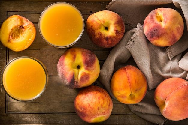 Натуральный персиковый сок в стакан на деревянный стол сверху