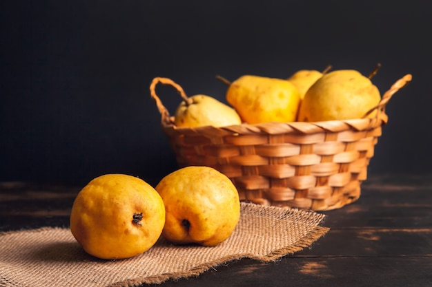 Natural pear fruit with defects in a basket on a jute napkin and a dark wooden background.