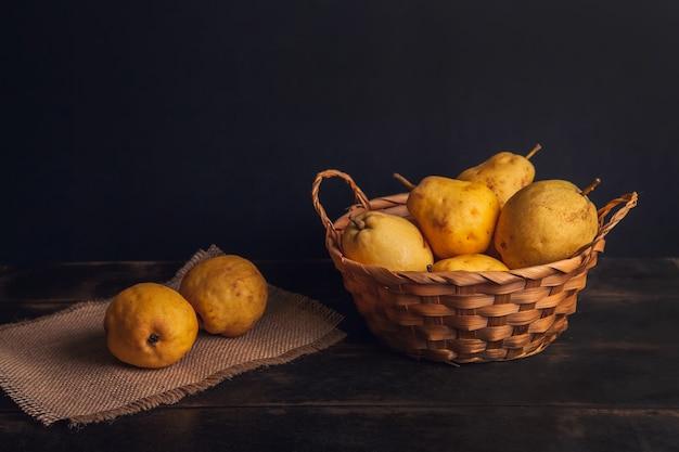 Натуральные плоды груши с дефектами в корзине на джутовой салфетке и темном деревянном фоне.