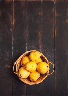 Натуральные плоды груши с дефектами в корзине на темном деревянном фоне.