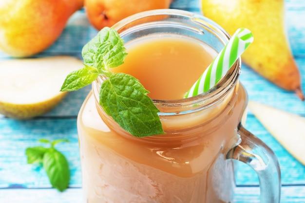 ガラスカップに入った天然梨ジュース。ジューシーで熟した会議梨とミントの葉。明るい青色の背景。