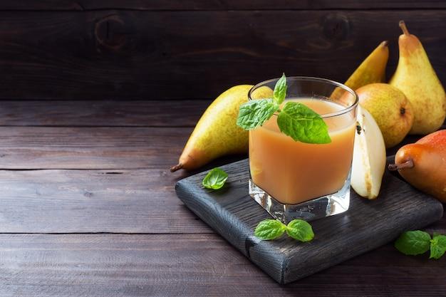 ガラスカップに入った天然梨ジュース。ジューシーで熟した会議梨とミントの葉。コピースペース暗い素朴な木製の背景。
