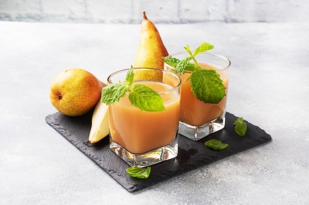 ガラスカップに入った天然梨ジュース。ジューシーで熟した会議梨とミントの葉。コピースペーススレートスタンド、明るいコンクリートの背景。