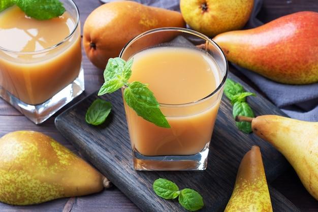 ガラスカップに入った天然梨ジュース。ジューシーで熟した会議梨とミントの葉。暗い素朴な木製の背景。