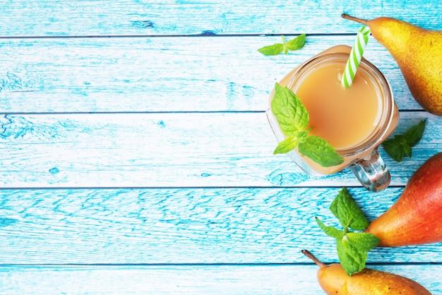 ガラスカップに入った天然梨ジュース。ジューシーで熟した会議梨とミントの葉。トップビューコピースペース明るい青色の背景。