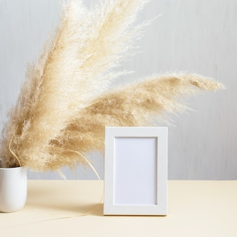 Natural phragmites plant in vase, wooden white photo frame on the beige table. modern interior element, eco friendly life style.