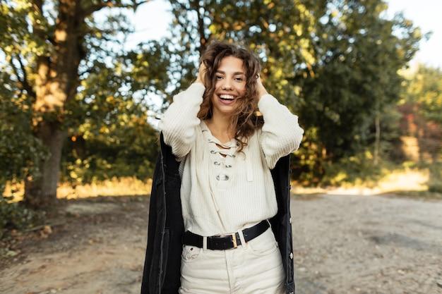 청바지 재킷과 니트 스웨터를 입은 패션 데님 옷에 곱슬머리를 한 웃고 있는 아름다운 행복한 여성의 자연스러운 초상화가 시골을 걷고 있습니다. 여성 캐주얼 스타일