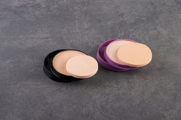 Natural powder foundation with sponges placed on stone surface.