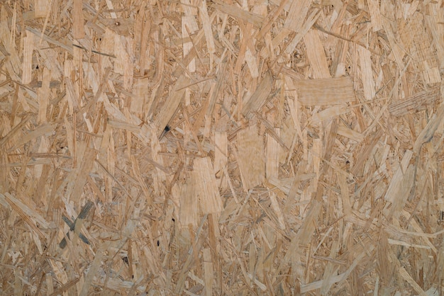 Natural pressed sawdust close-up. background image of sheet of plywood with fragments of compressed sawdust. wooden texture template.