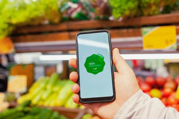 천연 제품. 한 남자가 슈퍼마켓 쇼케이스에서 신선한 채소를 배경으로 화면에 라벨이 붙은 스마트폰을 들고 있습니다. 환경 친화적이고 건강한 음식.