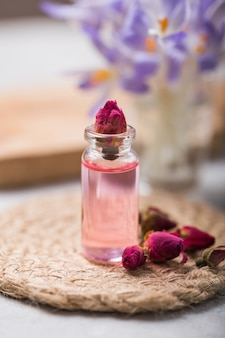 Natural pure rose oil or scented water in bottles for spa, skin care or aromatherapy with pink roses  dry. organic cosmetics concept. selective focus